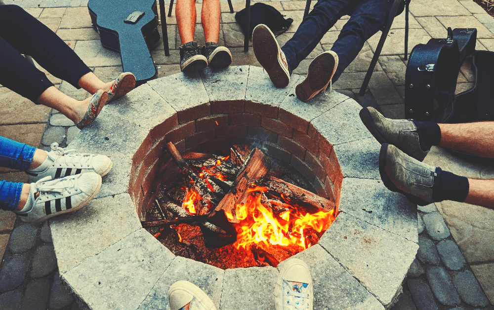 fire burning in a stone fire pit with several people sitting around it