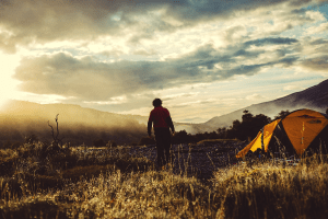 man walking by his tent