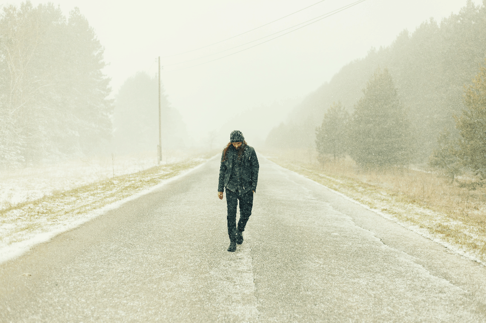 man walking down the road in snow
