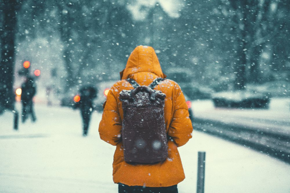 man in a coat wearing a backpack walking through the snow