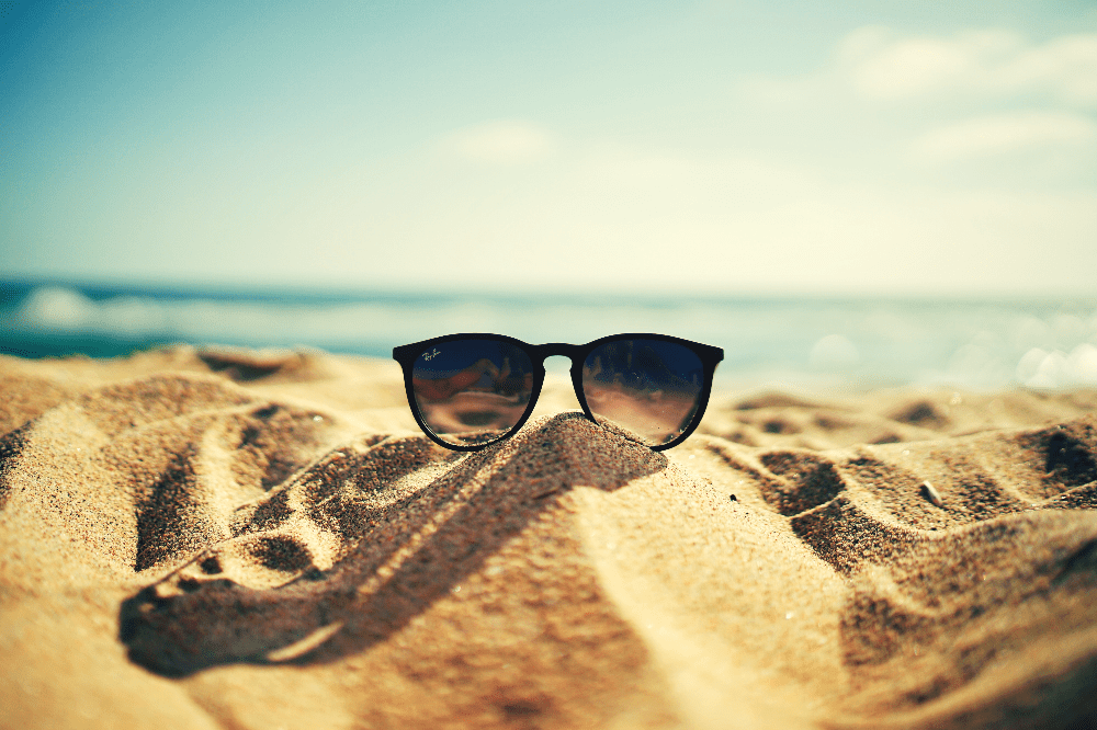 a pair of sunglasses resting on a pile of sand on the beach