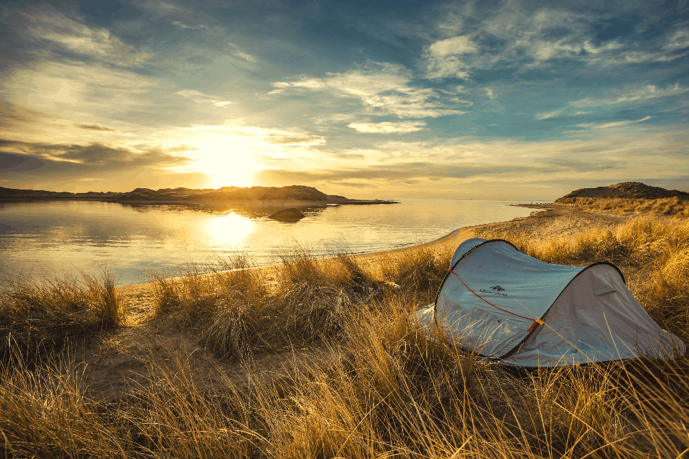 tent on a plain overlooking the sunset