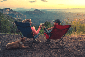 two people sitting in camping chairs