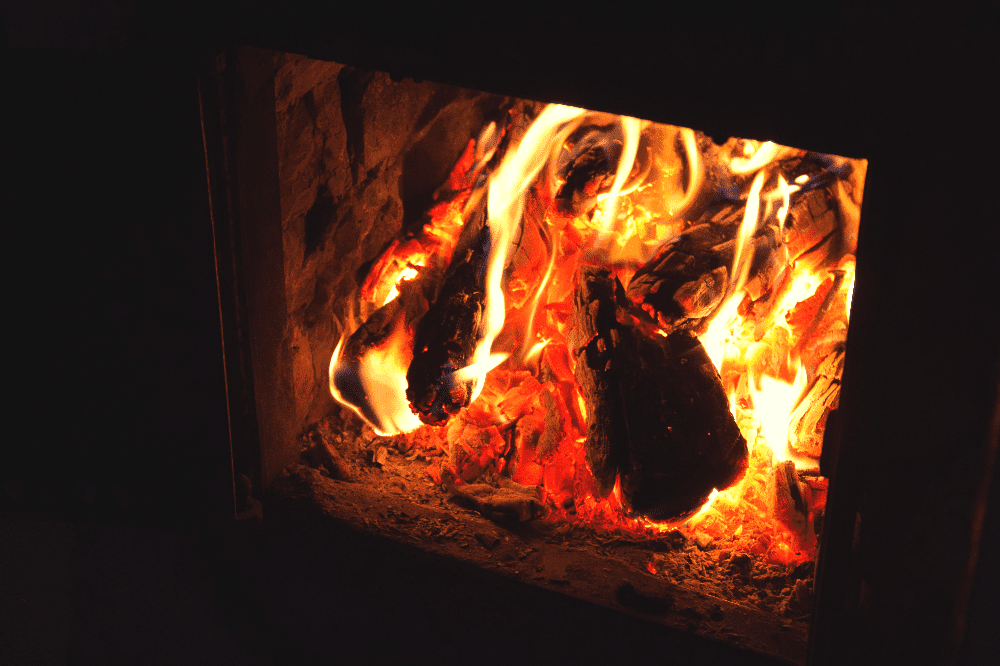 logs burning inside of a wood fire stove