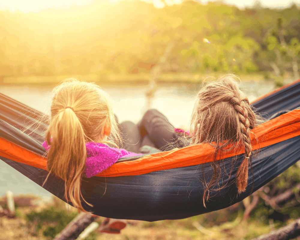 two sisters sitting in a hammock