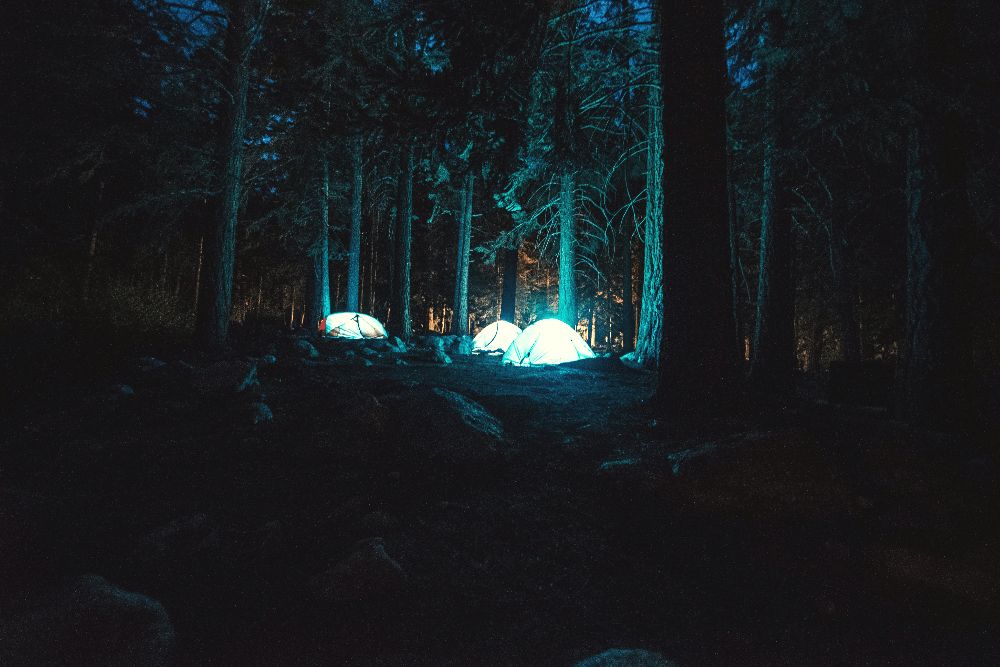 three tents with lights at night
