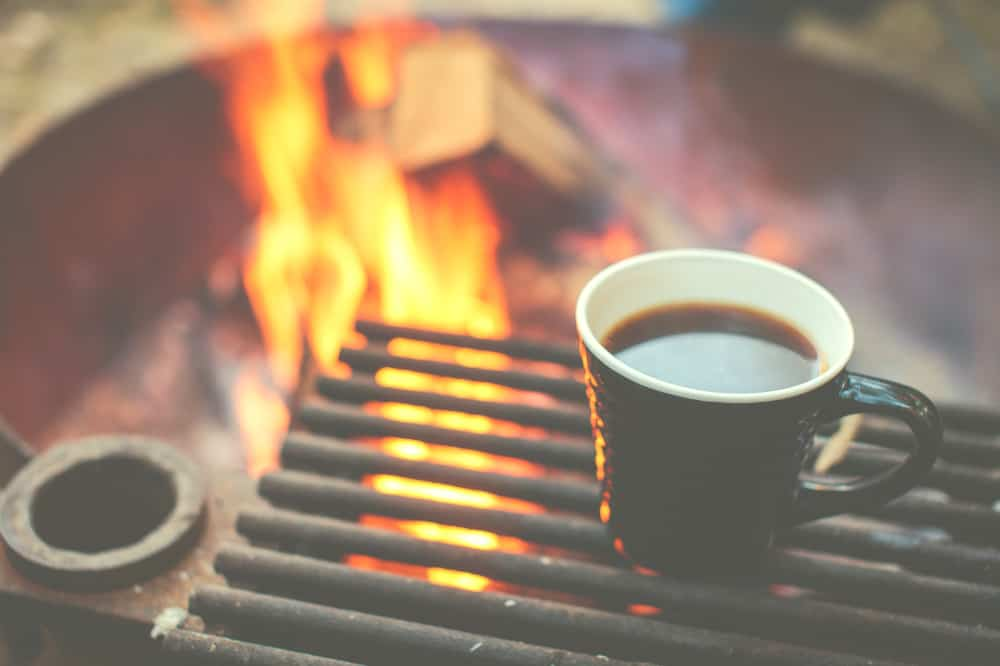 coffee in a cup next to a campfire