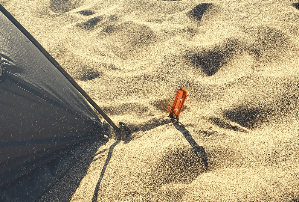 tent stake buried in the sand