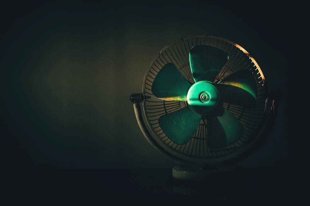 fan sitting on a desk in the dark