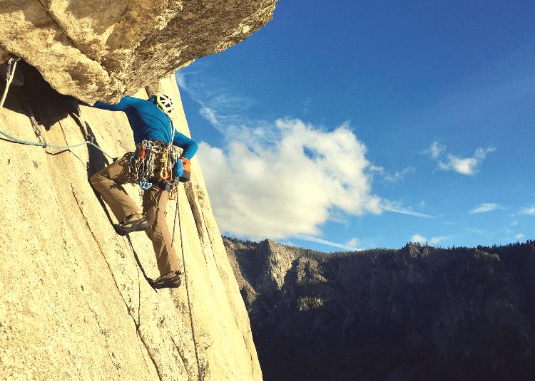 man traversing while trad climbing