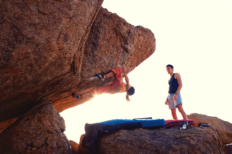 two people bouldering at sunrise