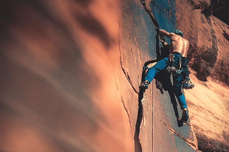 man trad climbing a crack
