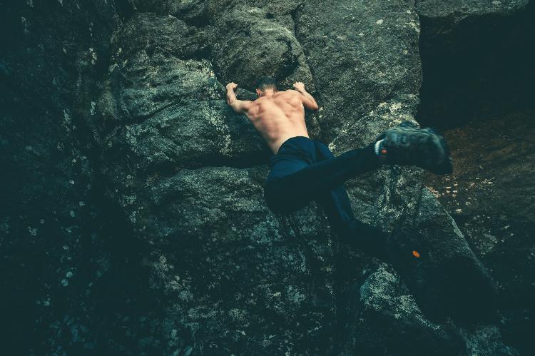 shirtless man bouldering