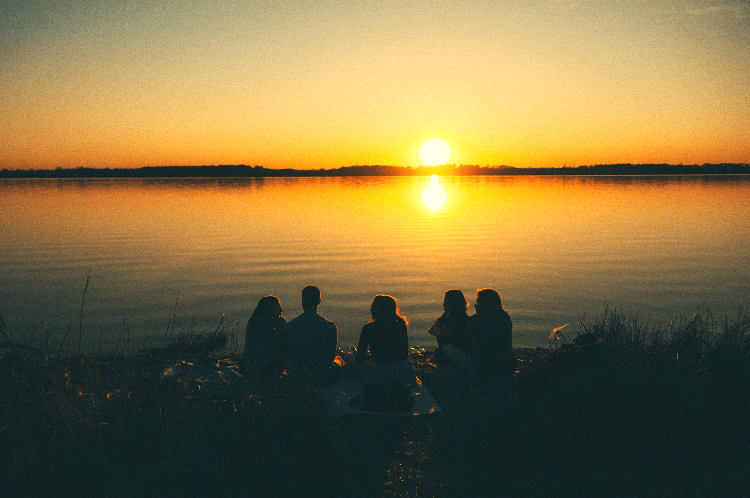 group of people around a lake at sunset