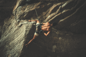 man rock climbing shirtless