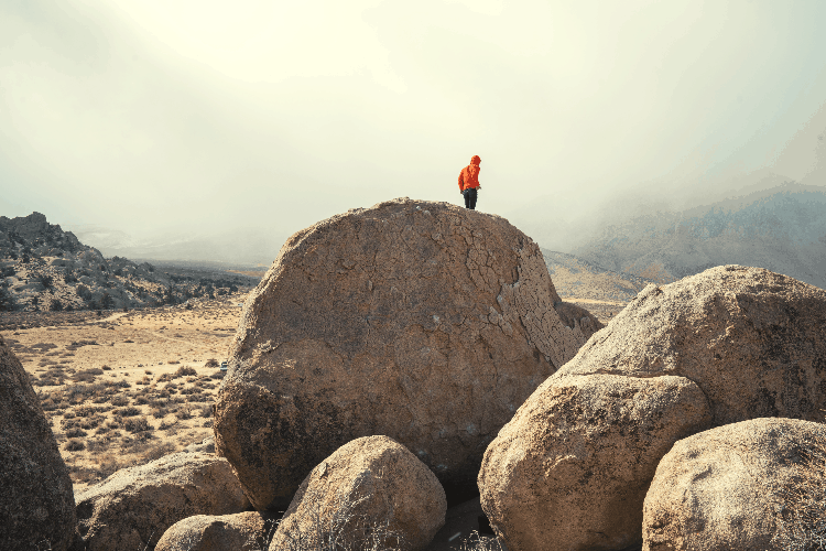 man on top of a large boulder