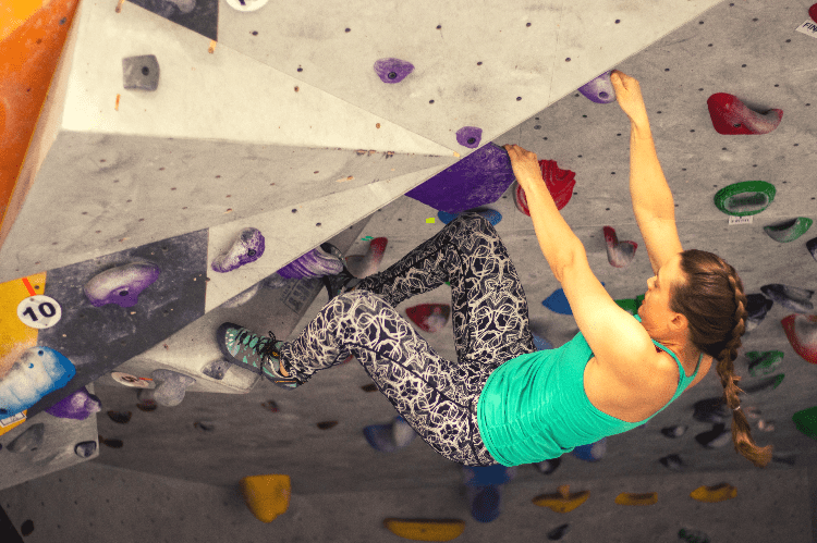 woman bouldering in a gym