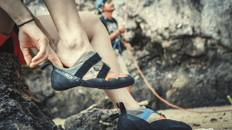 person putting their climbing shoes on