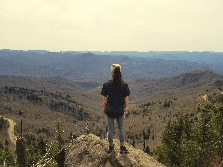 woman standing on top of a cliff