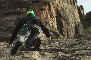 man rock climbing with a hat on