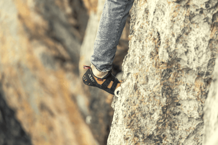 person wearing rock climbing shoes