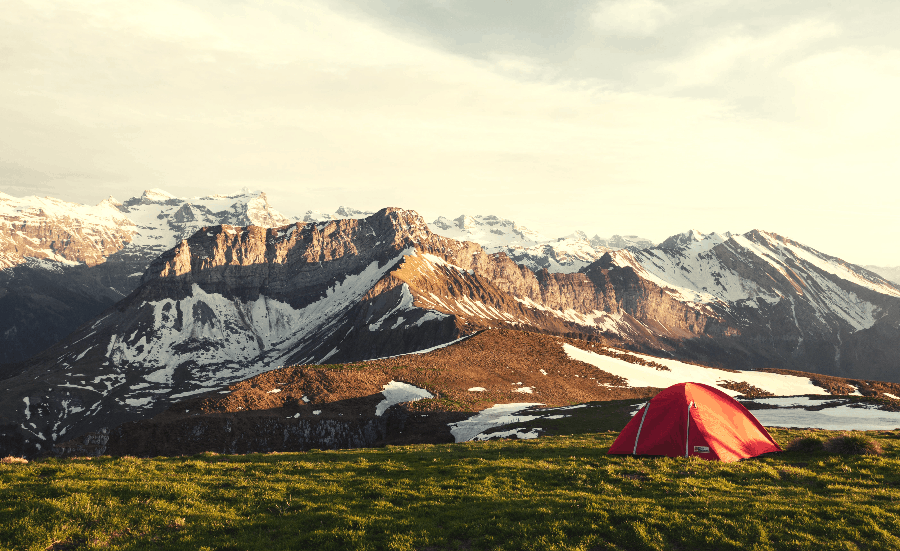 tent on a grassy plain next to mountains