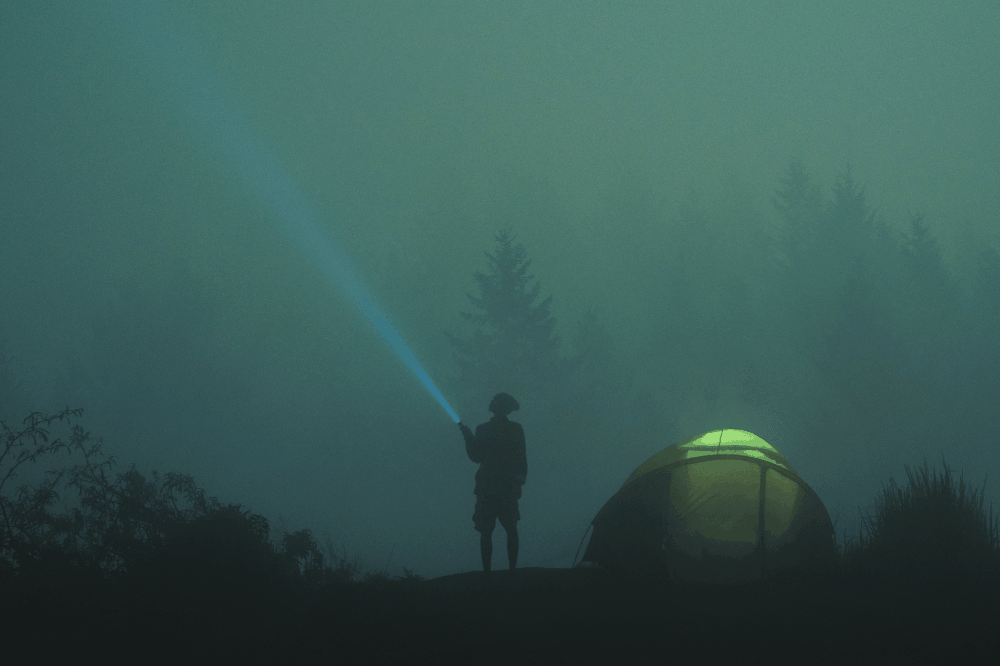 person next to a tent shining a light in bad weather