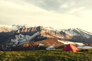 tent pitched on a grassy plain next to mountains