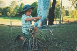 young boy putting sticks together to build a campfire
