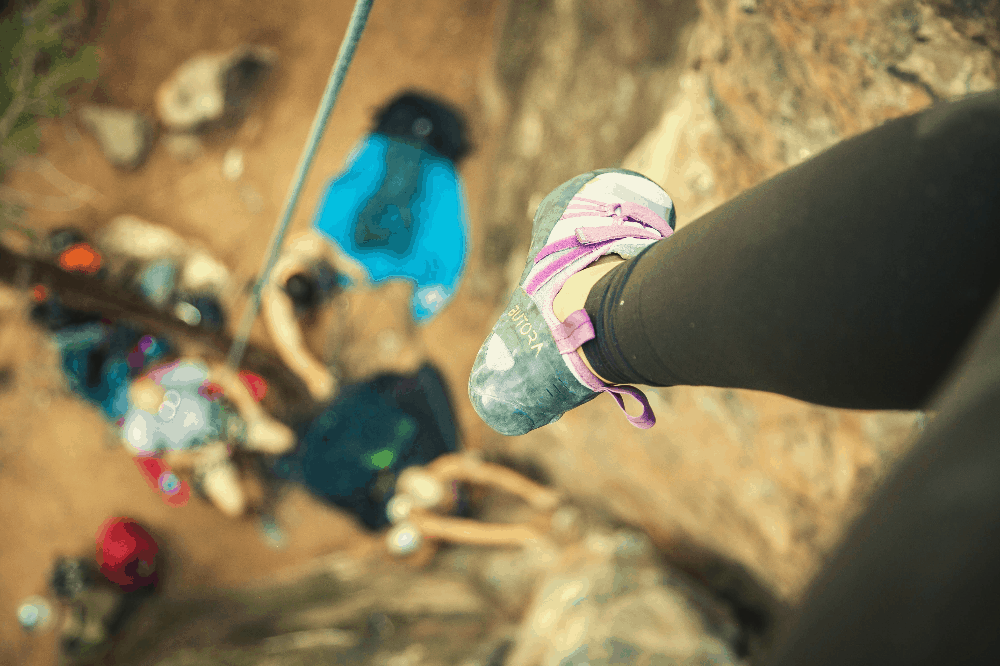 woman rock climbing with her shoes