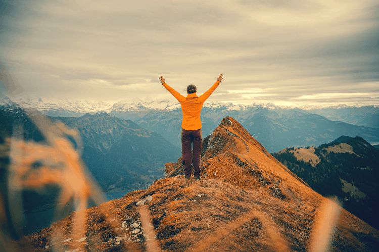 person with raised arms on top of a ridge