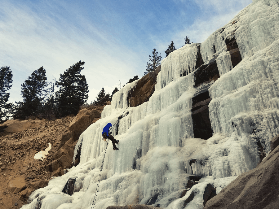 man rappelling down a frozen waterfall