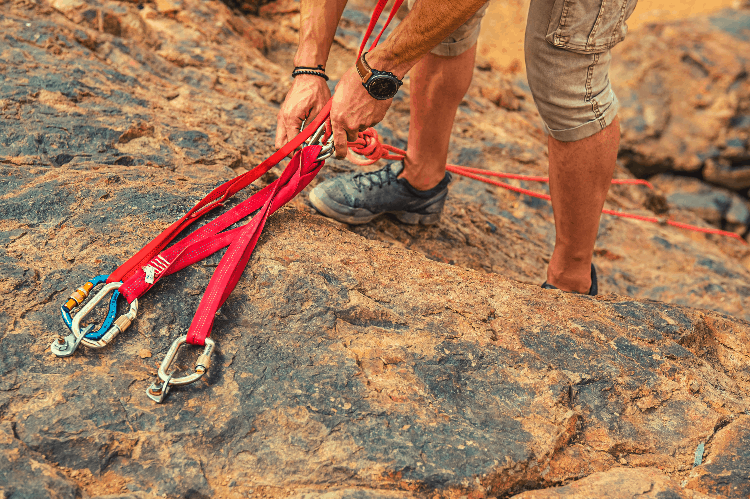 man building a rock climbing anchor