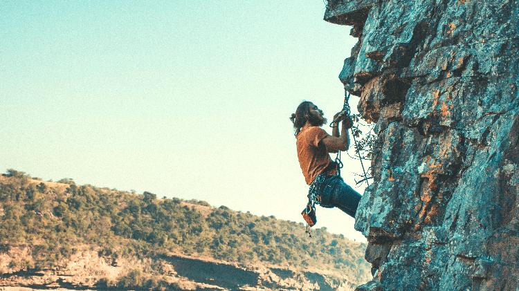 man doing anchor work while rock climbing