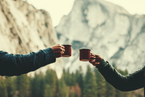two people holding cups of coffee in the mountains
