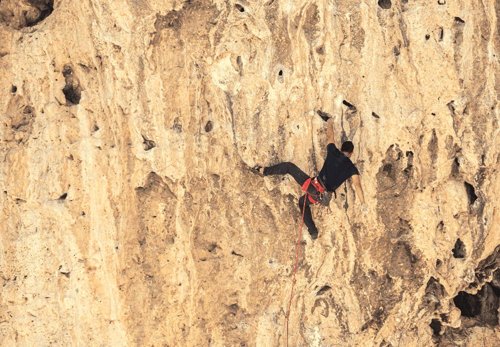 man sport climbing on a rock wall
