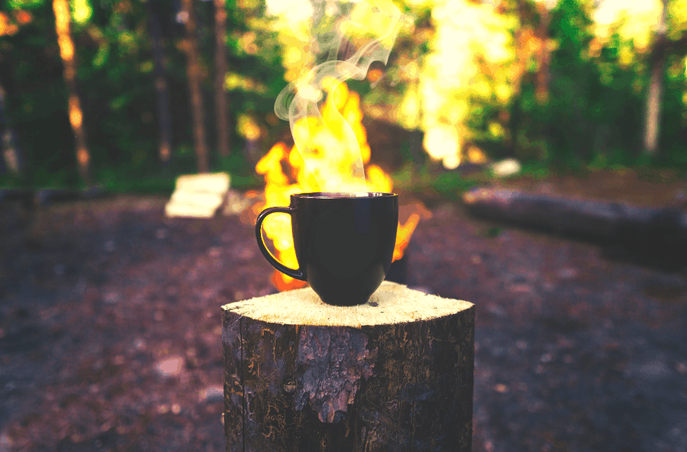 coffee mug on a stump in front of fire