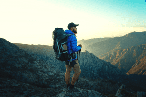 man in the mountains with a backpack