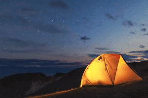 glowing tent on a ridge at dusk