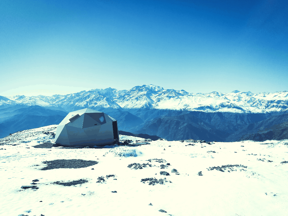 tent sitting in the snow on top of a mountain