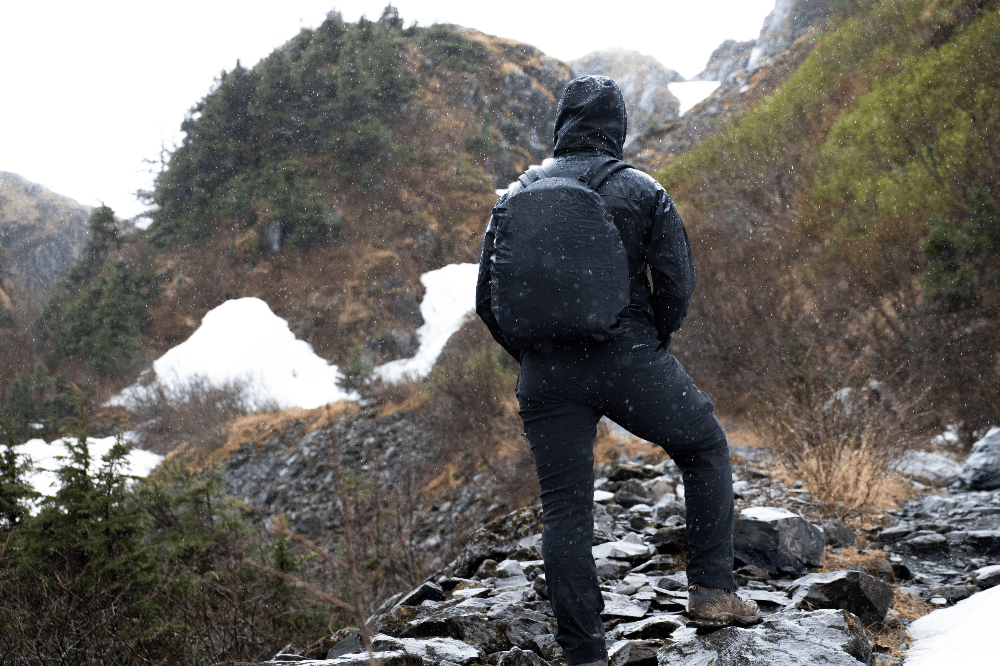 man standing in the rain with backpack