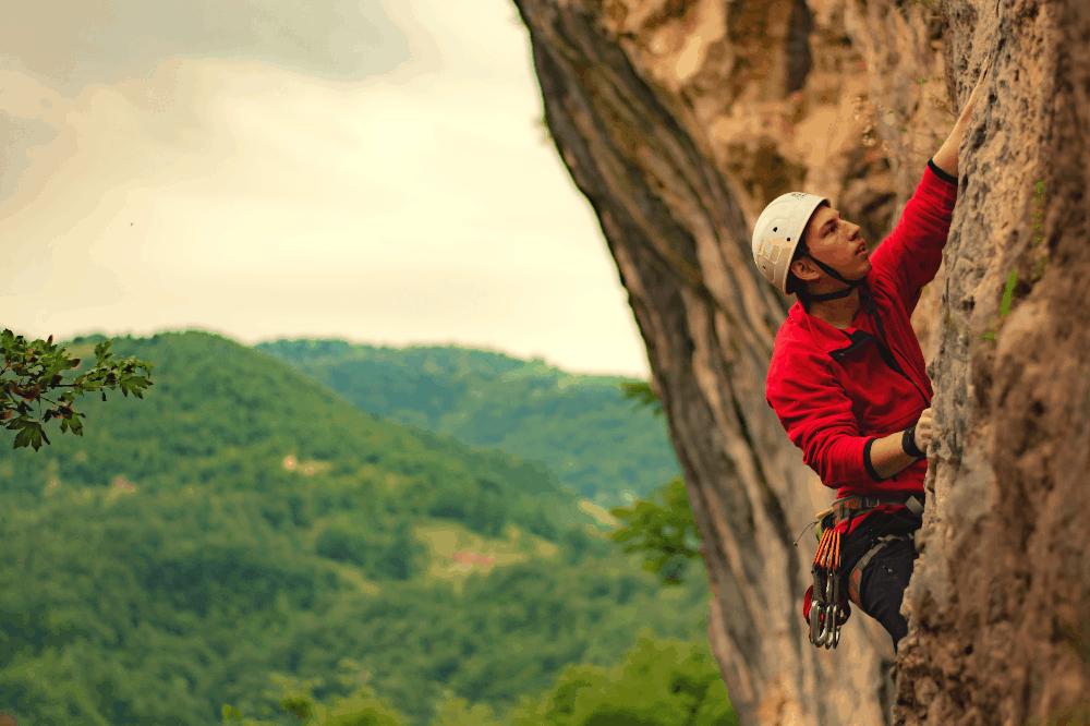 man rock climbing while wearing a helmet
