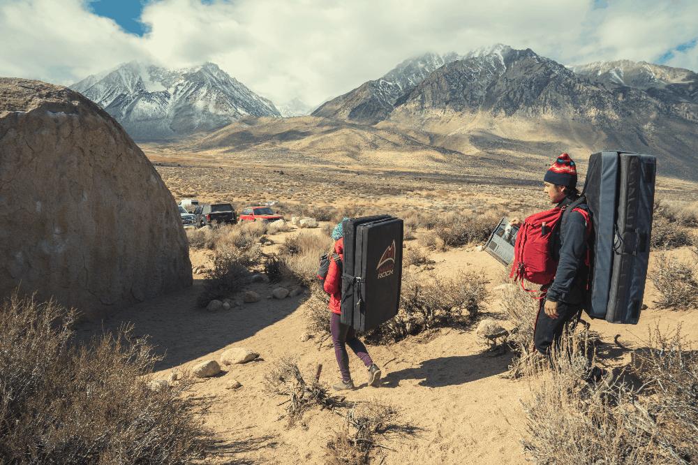 climbers carrying crash pads to a boulder