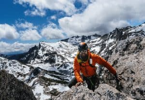 man alpine climbing with a helmet and coat on