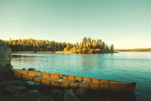 canoe sitting on the edge of a lake
