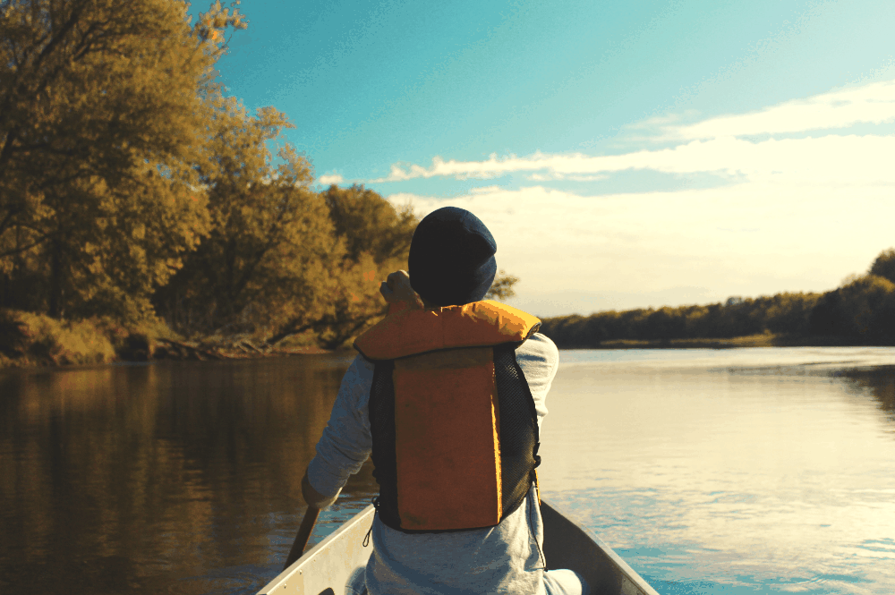 person sitting in a canoe on a lake