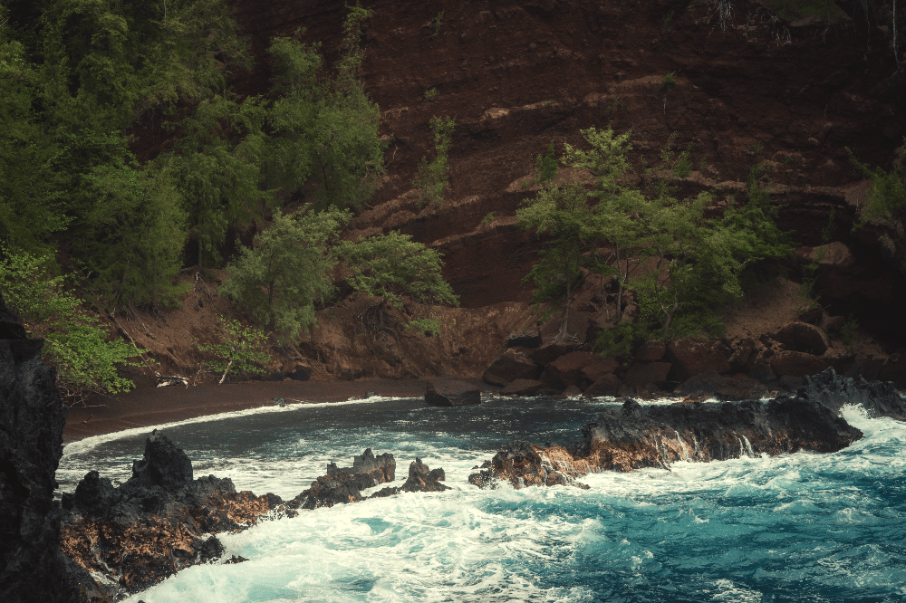 red sand beach next to ocean in hawaii