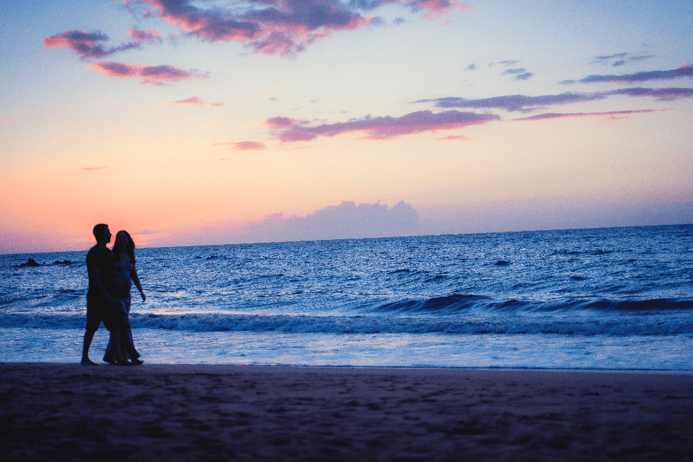 a couple strolling down a beach at sunset