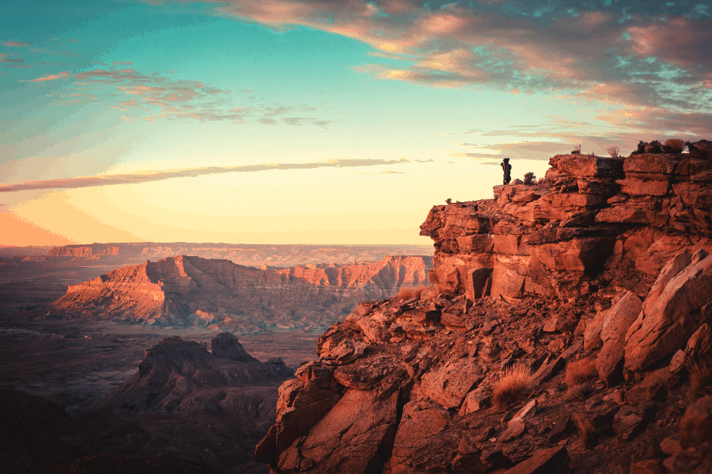 man standing on the edge of a sandstone cliff