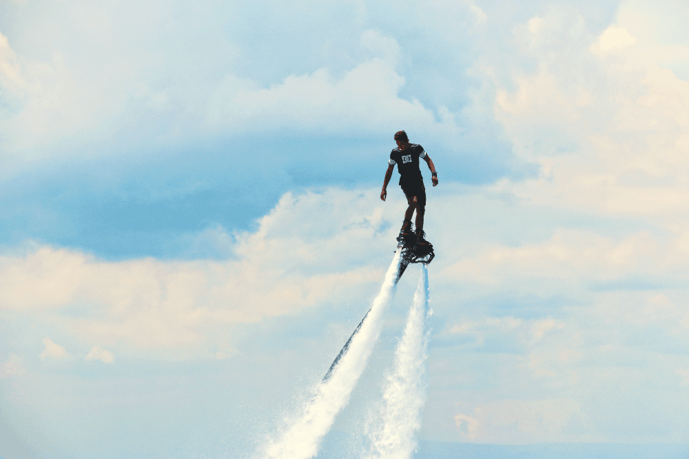 man standing on a flyboard in the air